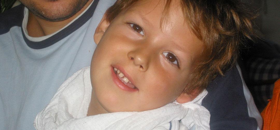 """Joshua liegt im Arm und lächelt. Ein typischer Gesichtsausdruck für """"Das finde ich toll!"""""""